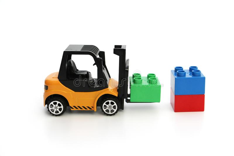 Kids toys. Yellow forklift toy ships color cubes royalty free stock images