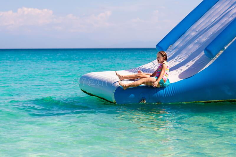 Kids on trampoline on tropical sea beach. Kids jumping on trampoline on tropical sea beach. Children jump on inflatable water slide. Aqua amusement park in royalty free stock image