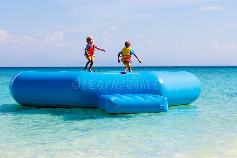 Kids on trampoline on tropical sea beach. Kids jumping on trampoline on tropical sea beach. Children jump on inflatable water slide. Aqua amusement park in stock images