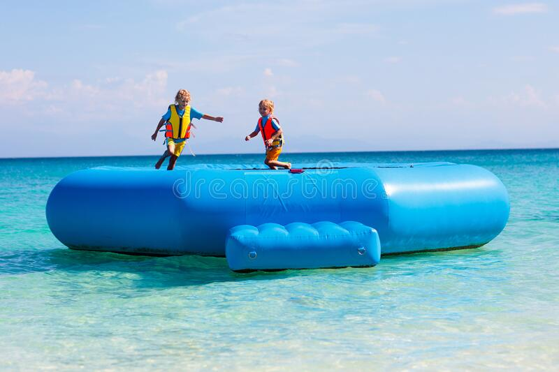 Kids on trampoline on tropical sea beach. Kids jumping on trampoline on tropical sea beach. Children jump on inflatable water slide. Aqua amusement park in royalty free stock photos