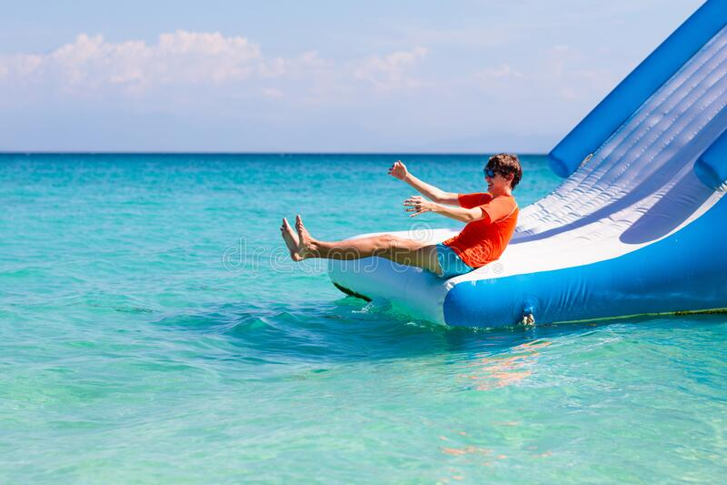 Kids on trampoline on tropical sea beach. Kids jumping on trampoline on tropical sea beach. Children jump on inflatable water slide. Aqua amusement park in stock photos