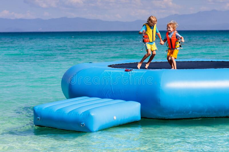 Kids on trampoline on tropical sea beach. Kids jumping on trampoline on tropical sea beach. Children jump on inflatable water slide. Aqua amusement park in royalty free stock images