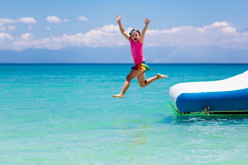 Kids on trampoline on tropical sea beach. Kids jumping on trampoline on tropical sea beach. Children jump on inflatable water slide. Aqua amusement park in stock image
