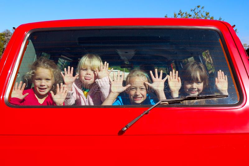 Kids in transit. Four Caucasian little girls having fun while looking out of the back window during their drive to a party in a red bus royalty free stock photos