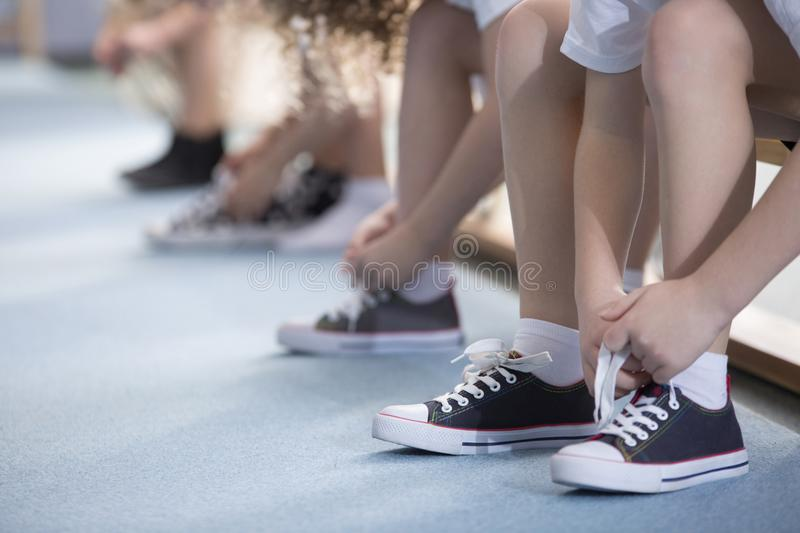 Kids tying sport shoes close-up royalty free stock photography