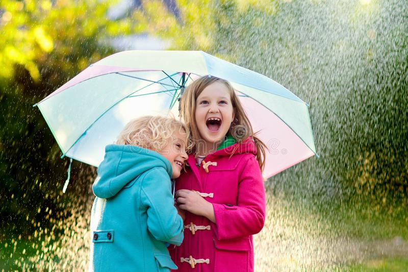 Kids with umbrella playing in autumn shower rain. Kids with colorful umbrella playing in autumn shower rain. Little boy and girl in warm duffle coat play in a stock photo