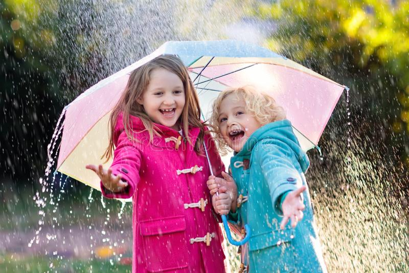 Kids with umbrella playing in autumn shower rain. Kids with colorful umbrella playing in autumn shower rain. Little boy and girl in warm duffle coat play in a stock images