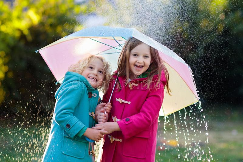 Kids with umbrella playing in autumn shower rain. Kids with colorful umbrella playing in autumn shower rain. Little boy and girl in warm duffle coat play in a stock photography