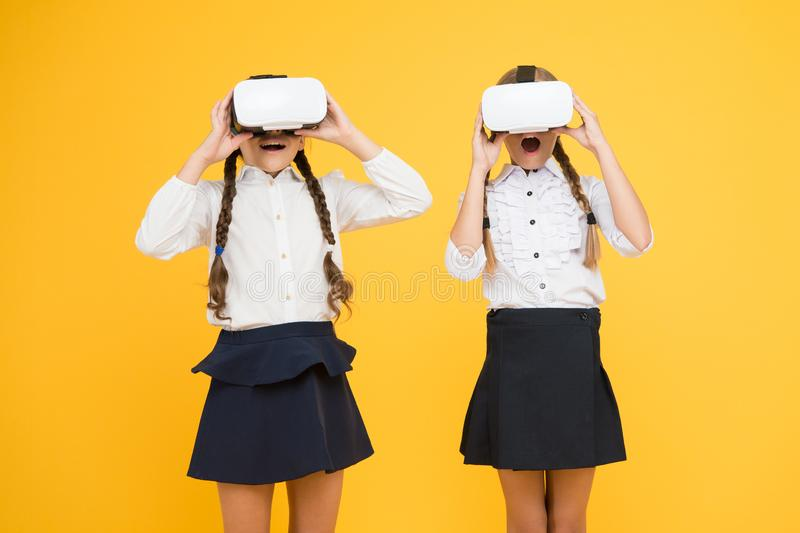 Kids use modern VR technology. Virtual reality. VR headset. Future education. Children schoolgirls wear wireless VR. Glasses. Exploring augmented reality royalty free stock images