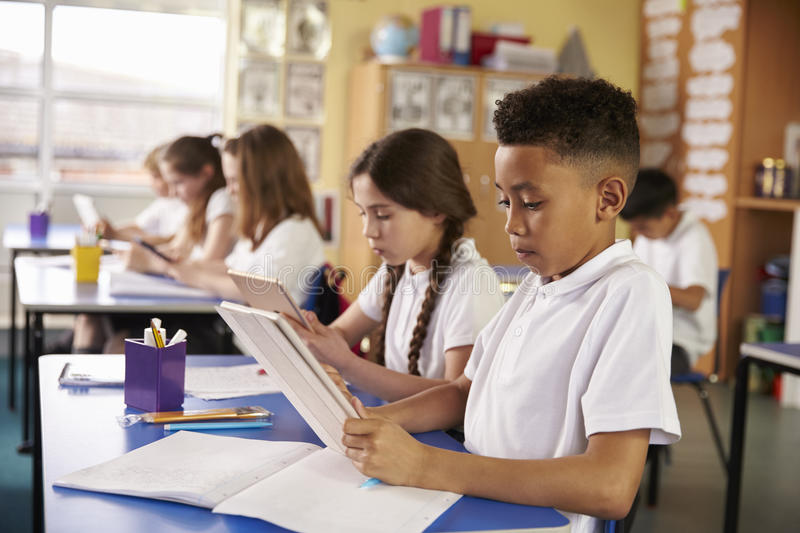 Kids use tablet computers in primary school class, close up stock photography