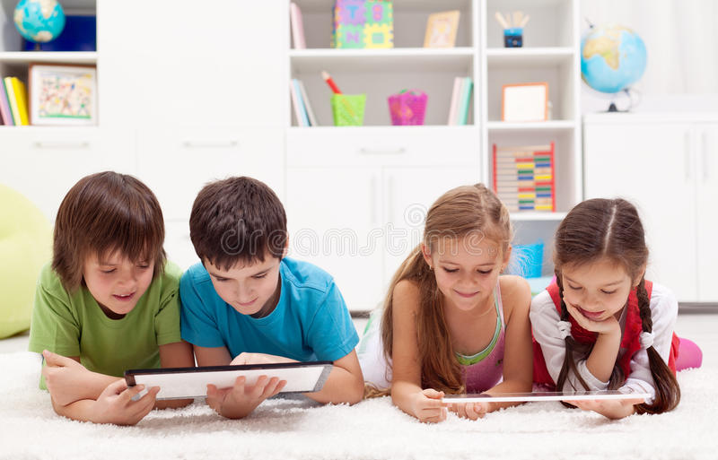 Kids using tablet computers. Kids using modern tablet computers laying on the floor