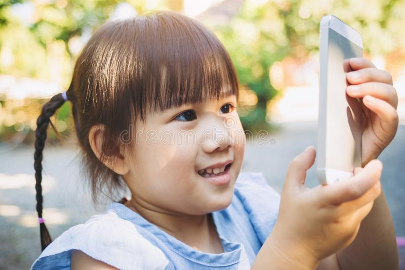 Kids using smart phone for take a photo and play game. royalty free stock photography