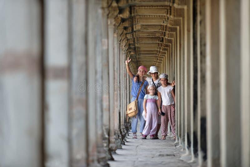 Kids visiting Angkor Wat, Cambodia. Kids in walkway among ruins of Angkor Wat, Cambodia royalty free stock image