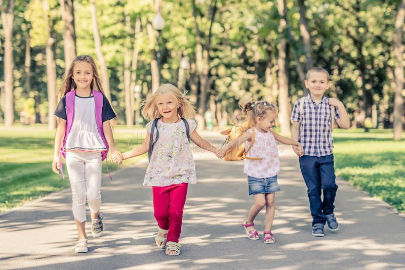 Kids Walking in the Park. Funny kids holding hands and walking together in the park royalty free stock photos