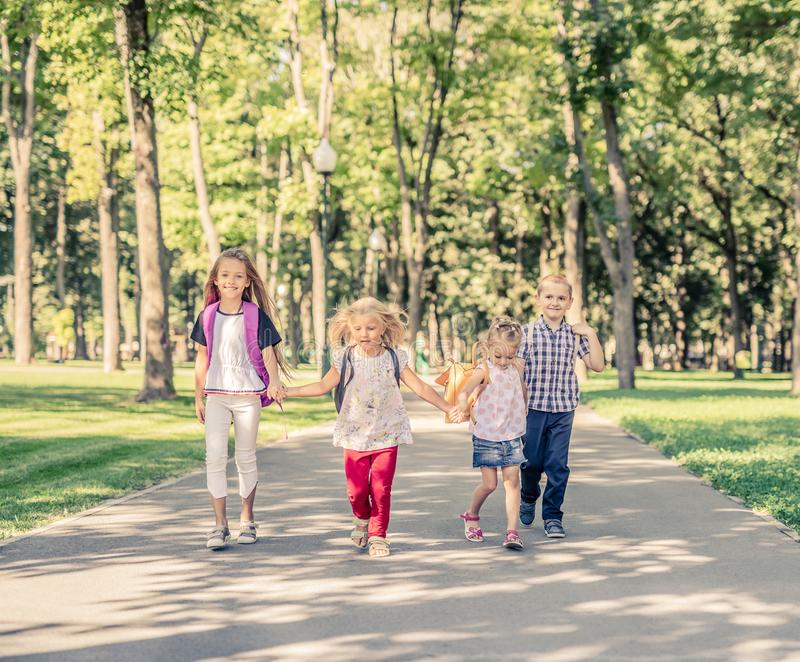 Kids Walking in the Park. Funny kids holding hands and walking together in the park stock photo