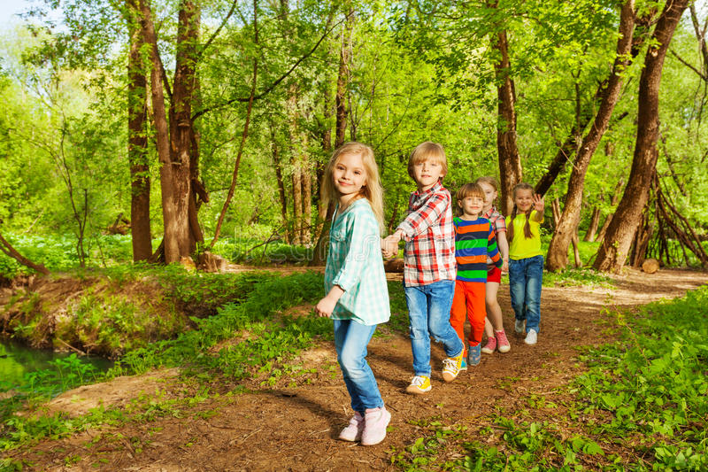 Kids walking in the summer forest holding hands. Portrait of cute kids walking in the green summer forest one after another holding hands stock photo