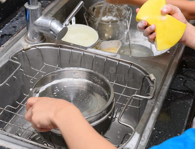Kids washing dishware in kitchen sink with soapy sponge. Kids washing dishware in the kitchen sink with soapy sponge royalty free stock image