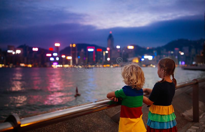 Kids watch Hong Kong harbor skyline. At night. Travel with young children. Beautiful view of skyscraper and sea harbor at sunset stock photography