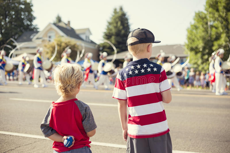 Kids watching an Independence Day Parade. A rear view of kids watching a marching band walk by during a parade procession during an Independence Day parade in a royalty free stock photos