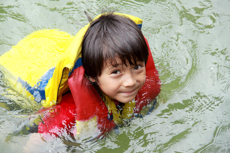 Kids in the water. Cheerful kids in the water wearing life vest smiling at camera stock photos