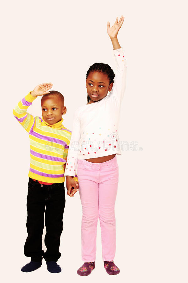 Kids wave a sad farewell. Two beautiful kids wave a sad farewell, vertical composition with text space stock images