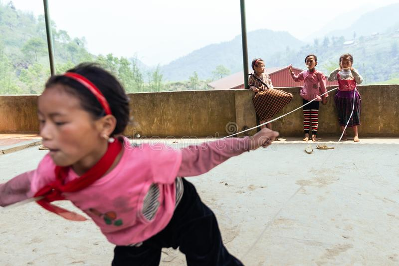 Kids wearing pink t-shirt play rope jump on concrete floor in summer at Sa Pa, Vietnam stock images