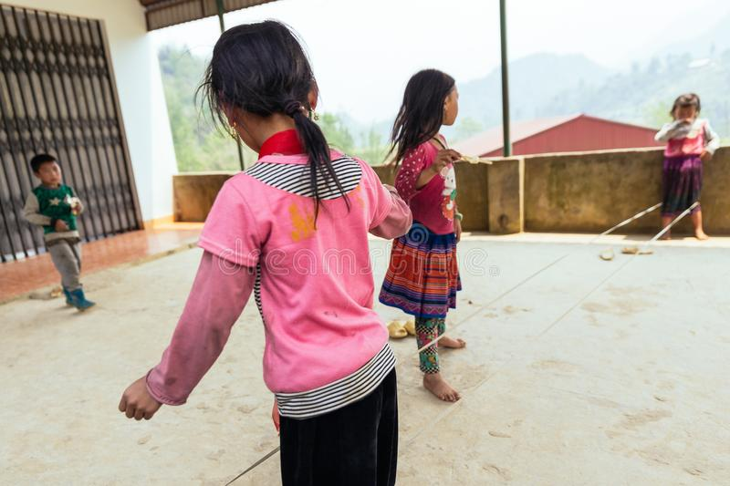 Kids wearing pink t-shirt play rope jump on concrete floor in summer at Sa Pa, Vietnam stock photography