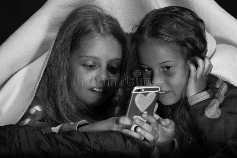 Kids wearing red jammies in bed on black background. First love and friendship concept: girls under blanket with phone royalty free stock photo