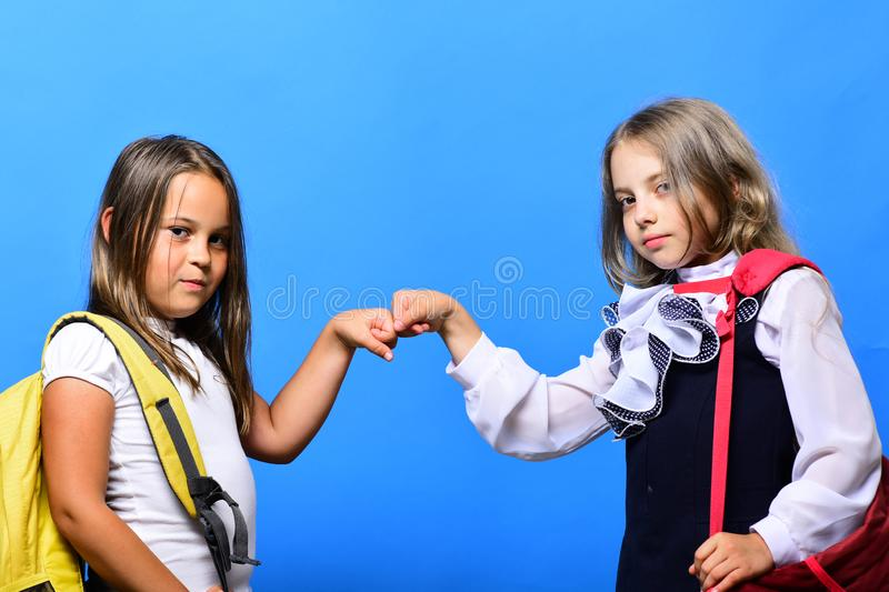 Kids wearing schoolbags beat each others fists. Schoolgirls in school clothes on blue background. Girls with confident faces and loose hair. Classroom and back royalty free stock photos
