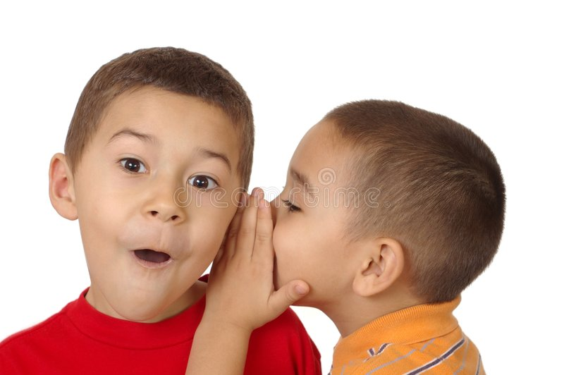 Kids whispering, 5 and 6 years. Two boys, aged five and six years, share a secret as one whispers in the other's ear, isolated on white background stock photography