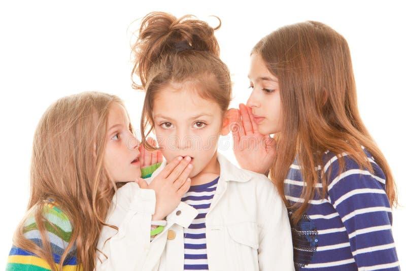 Kids whispering bad news stock photography