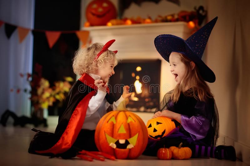 Kids in witch costume on Halloween trick or treat. Little girl in witch costume and boy dressed up as vampire on Halloween trick or treat. Children trick or royalty free stock photo