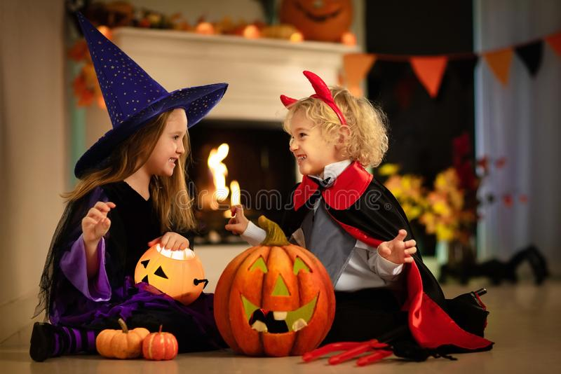 Kids in witch costume on Halloween trick or treat. Little girl in witch costume and boy dressed up as vampire on Halloween trick or treat. Children trick or royalty free stock images