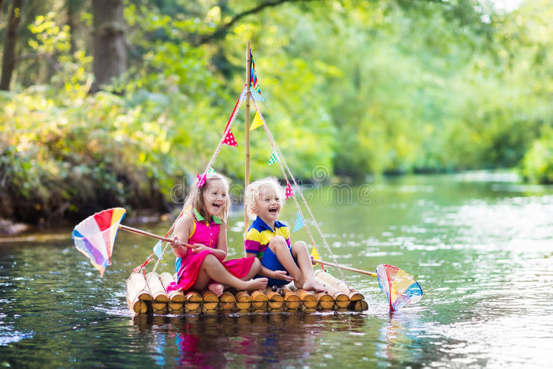 Kids on wooden raft royalty free stock photo