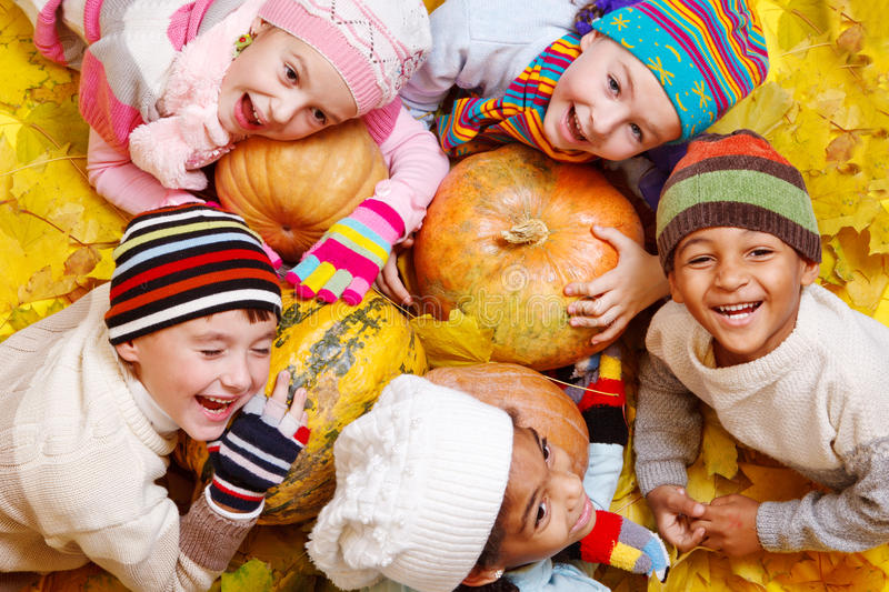 Kids on yellow leaves stock images