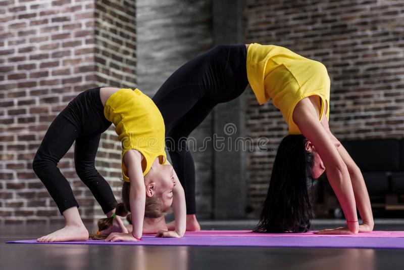 Kids yoga female teacher training a child girl standing in wheel pose working out in stylish sports studio royalty free stock photos