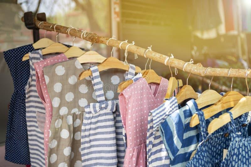 Kidss mode, gullig liten flickaklänning som hänger på trästången royaltyfria bilder