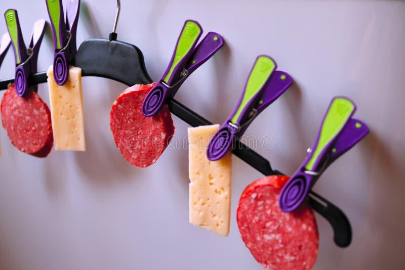 Kiełbasa i ser na wieszaku wieszaliśmy na czopach, kiełbasie i pokrojonym serze, zdjęcie stock