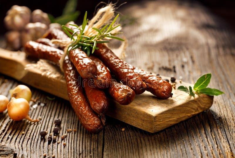 Kiełbasy na drewnianym wieśniaka stole z dodatkiem świezi aromatyczni ziele i pikantność, naturalny produkt od organicznie gospod zdjęcia stock