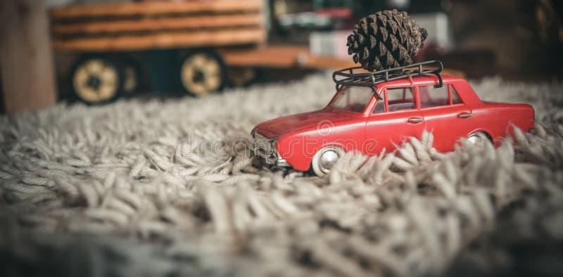 Kiefernkegel des Spielzeugautos tragender Weihnachts stockfotografie