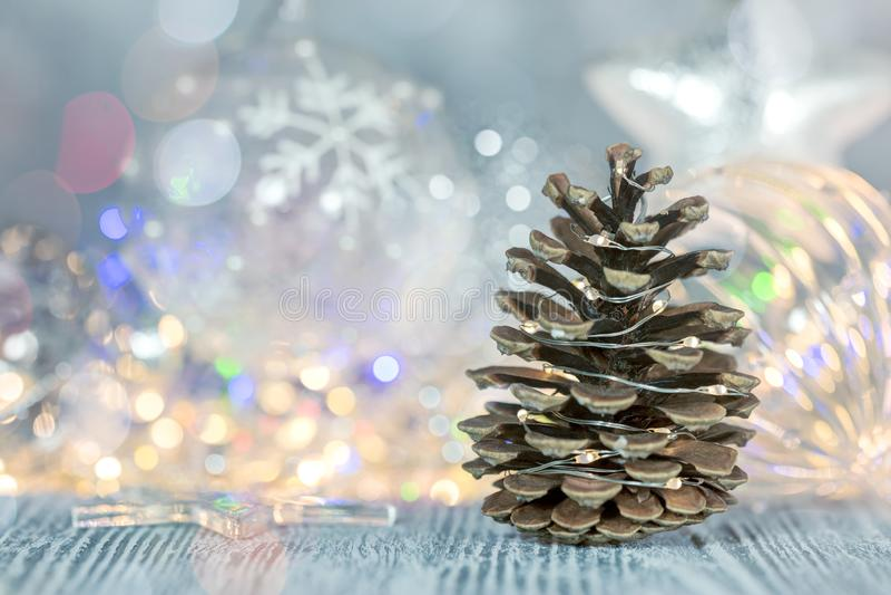 Kiefernkegel mit Weihnachtsglaskugeln auf glühendem Lichter backgroun lizenzfreie stockbilder