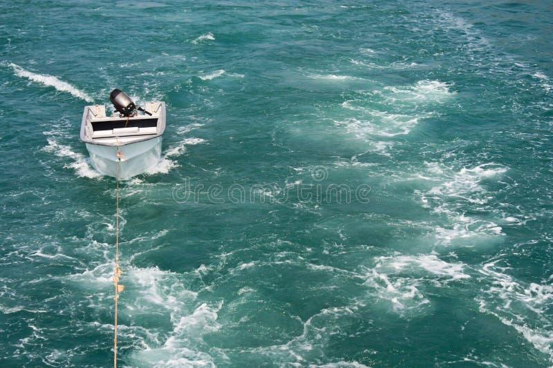 Kielzog van een motorboot met een kleine boot die wordt gesleept stock foto's