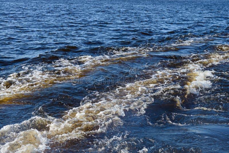 Kielzog van een motorboot op het water stock foto's