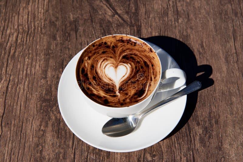 Kierowa kawowa sztuka na cappuccino w białym filiżanki i srebra tespoon na brown drewnianym stole fotografia royalty free