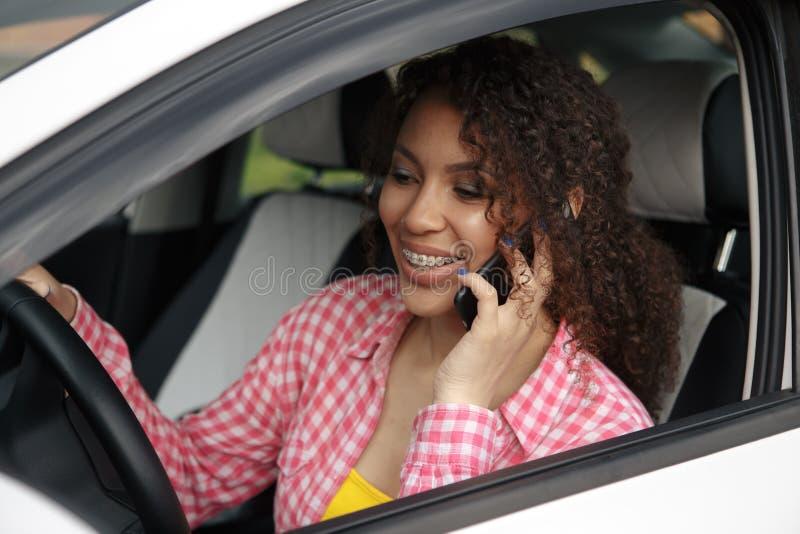 Kierowca kobieta jedzie samochód rozpraszającego uwagę na telefonie i patrzeje stronę zdjęcie stock
