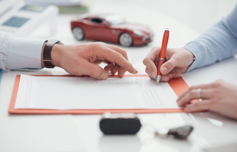 Kierowca podpisuje ubezpieczenie samochodu zdjęcia royalty free