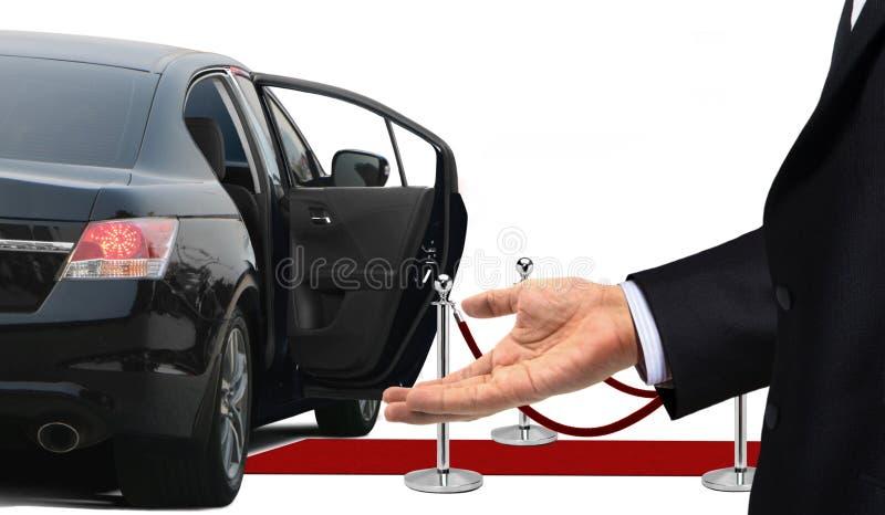 Kierowca pozycja z mile widziany gestem obok limuzyny fotografia stock