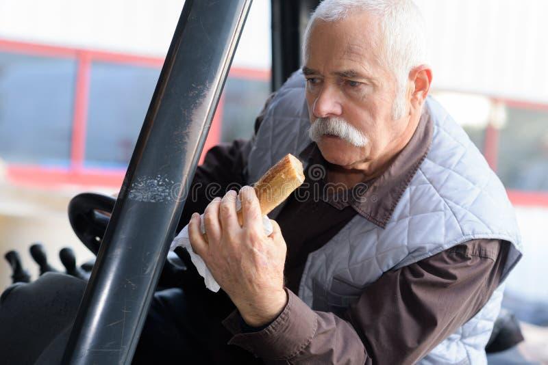Kierowcy łasowania chleb podczas gdy jadący klasycznego ciągnika zdjęcie stock