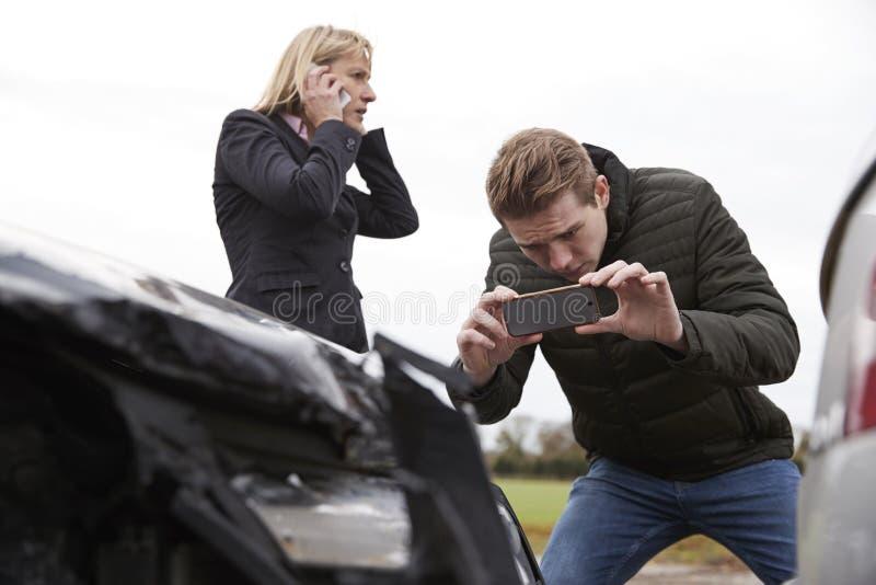 Kierowcy Bierze fotografię wypadek samochodowy Na telefonach komórkowych obraz stock