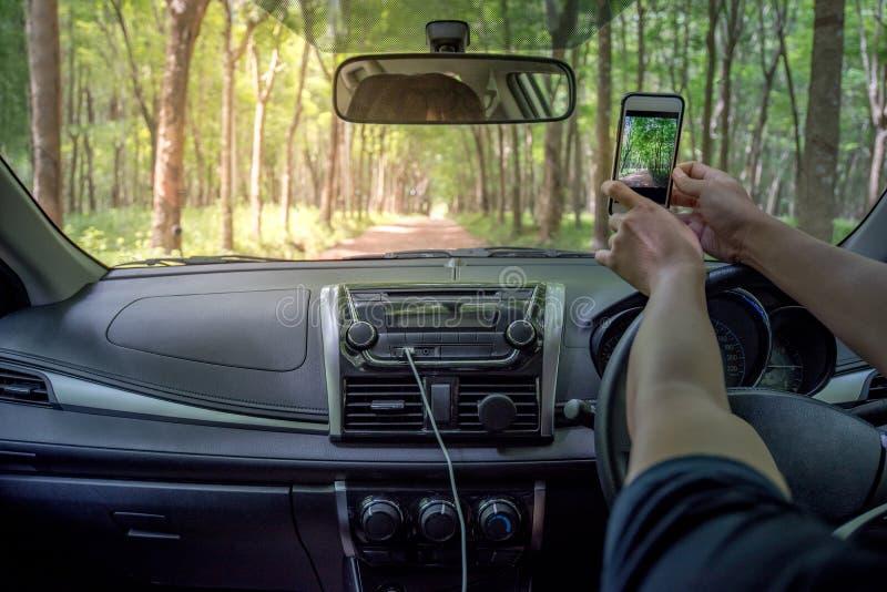 Kierowcy ` s wręcza brać fotografię od smartphone wśrodku samochodu zdjęcia stock